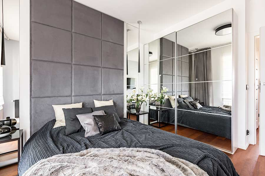 Mirrored wardrobe doors make this bedroom feel larger